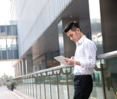 young asian businessman using tablet at office exterior