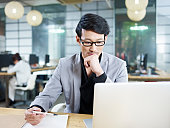 young asian business man working in office using laptop computer.