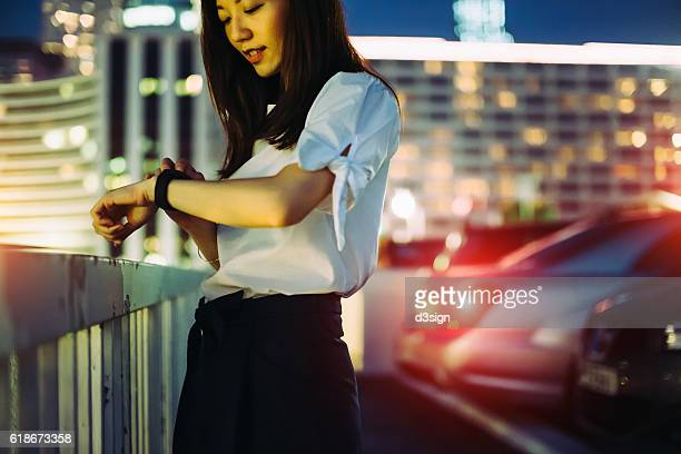 Young Asian businesswoman checking her smart watch in the city at night
