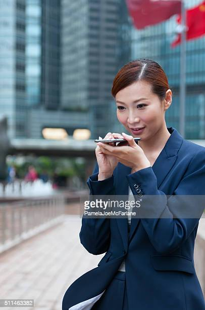 Young Asian Businesswoman Speaking into Smartphone, Hong Kong Financial District