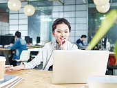young asian business woman working in office using laptop computer.