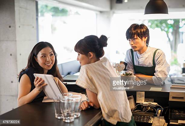 Young asian cafe owner using iPad