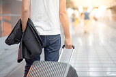 Young Asian casual man holding suit and luggage while walking in airport terminal