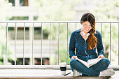 Young Asian college student girl reading book for exam, sitting at university campus with copy space. Education or casual studying lifestyle concept