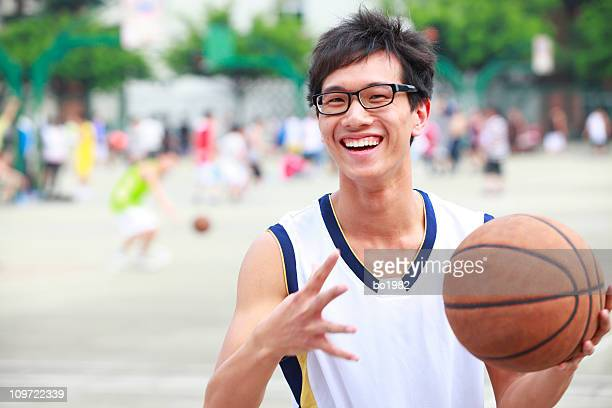young asian college student playing basketball