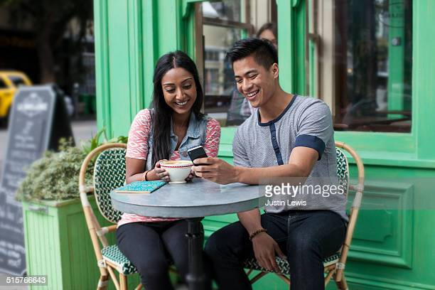 Young Asian couple at cafe smiling at phone
