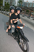 Young Asian couple on moped