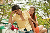 Young Asian couple relaxing on classic scooter