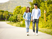 young asian couple walking on rural road, hand in hand.