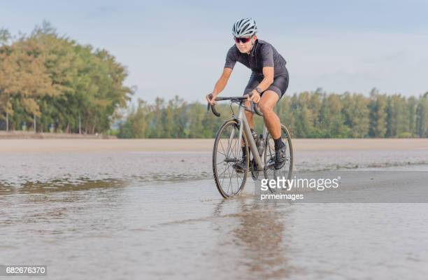 Young asian cyclist man ride  bicycle  the beach at the sunset