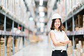 Beautiful young Asian engineer or technician smiling, warehouse or factory blur background, industry or logistic concept, with copy space