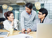 a team of young asian entrepreneurs having a discussion in office.