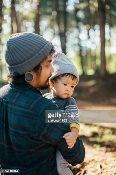 Junge asiatische Vater sein Baby in Holz im Winter zu tragen.