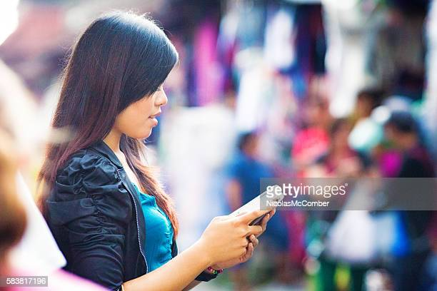 Young Asian female absorbed by her mobile AR video game