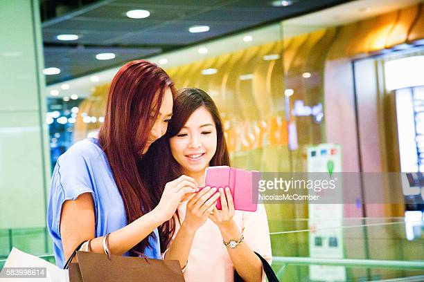 Young Asian female showing friend how to play mobile game