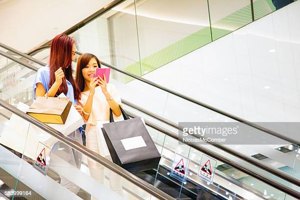 Young Asian female teaching mobile game with friend on escalator