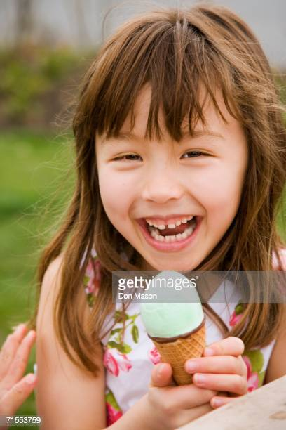 Young Asian girl eating ice cream cone