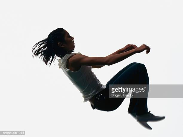 Young Asian girl in jeans & t-shirt, jumping in mid-air