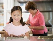 Young Asian girl in kitchen with grandmother