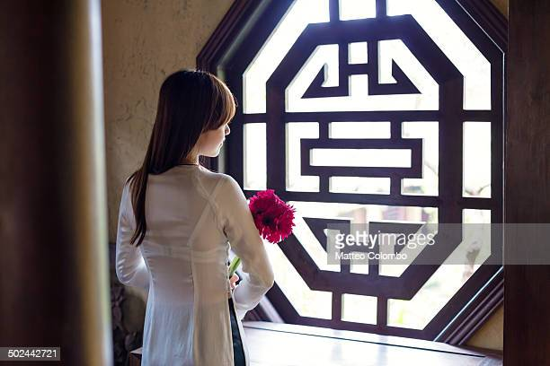 Young asian girl looking out of window