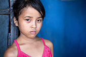 Young Filipina girl 8 years old with sad and somber expression over blue, poverty in the Philippines.