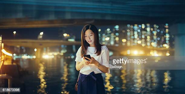 Young Asian girl using smartphone in front of the Hong Kong city skyline at night