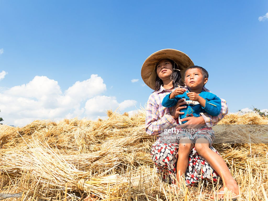 Young asian girl with baby boy in a crop field : Stock Photo