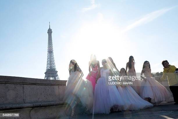 Young Asian girls wear evening dresses for photos souvenirs in front of the Eiffel tower at sunrise in Paris on July 13 2016 / AFP / LUDOVIC MARIN