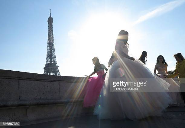TOPSHOT Young Asian girls wear evening dresses for photos souvenirs in front of the Eiffel tower at sunrise in Paris on July 13 2016 / AFP / LUDOVIC...