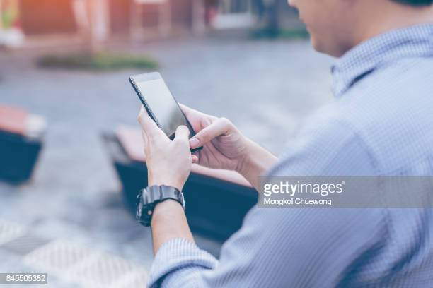 Young asian handsome businessman concentrated while reading his smartphone.