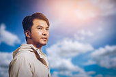 young asian handsome man looking to the future with hope on sky background