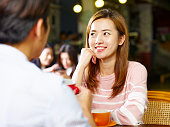 young asian couple lovers sitting at table chatting talking face to face in coffee shop.