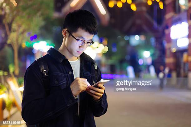 young asian man hold mobile phone on street at night