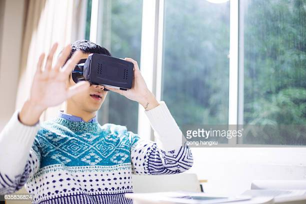 young asian man holds VR in classroom