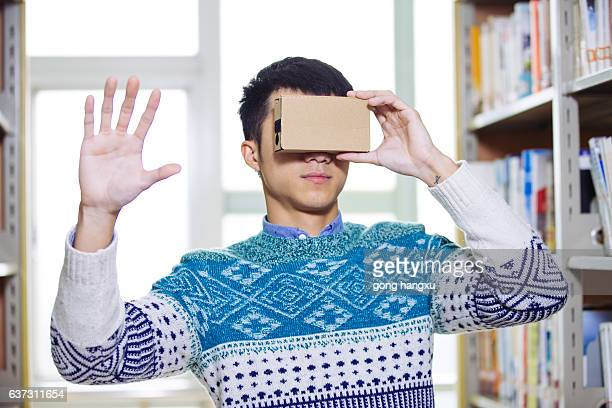 young asian man holds VR in library
