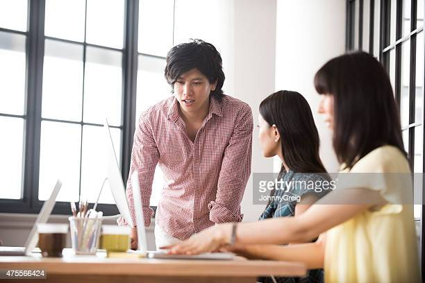 Young Asian man in discuusion with work colleagues