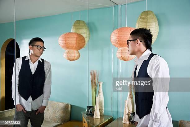 Jovem asiático homem olhando para o espelho