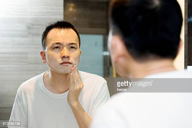 Young asian man shaving