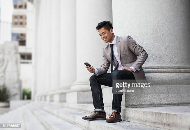 A young asian man smiling at his phone in city