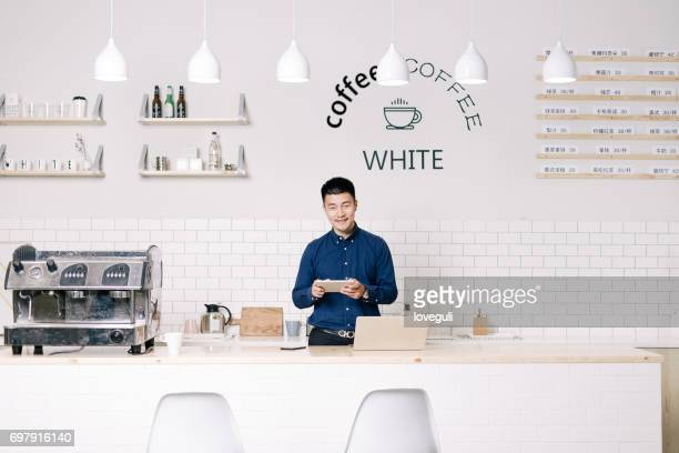 young asian man stands with tablet