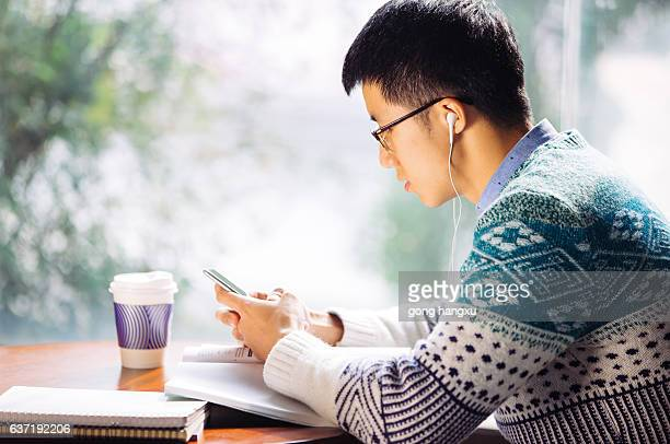 young asian man student holds mobile phone