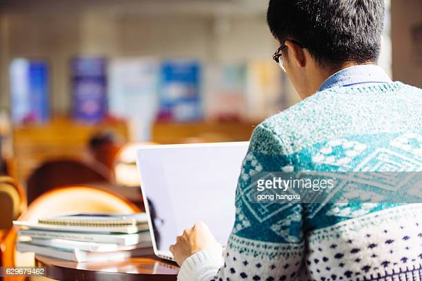 young asian man student using laptop