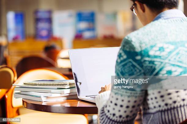 young asian man student using laptop