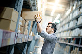 Young Asian man taking cardboard box from shelves in warehouse. Shopping warehousing or working pick and packing concepts