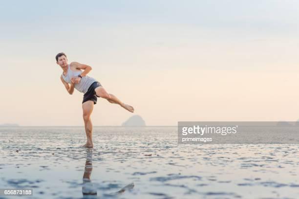 Young asian man training karate and kick boxing at the beach