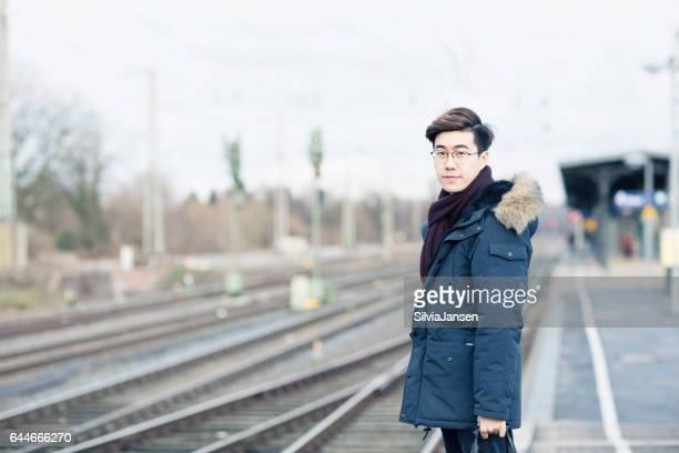 young asian man traveling with train