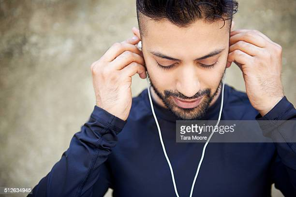young asian man using headphones