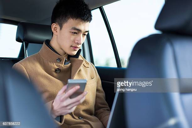 young asian man  using laptop in car