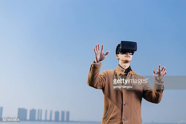 young asian man wearing VR in blue sky