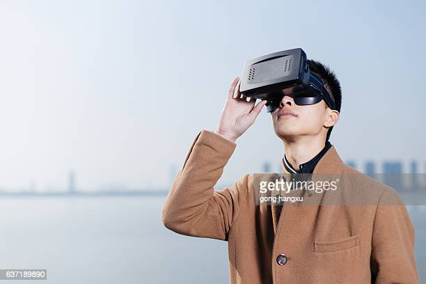 young asian man wearing VR near river in blue sky